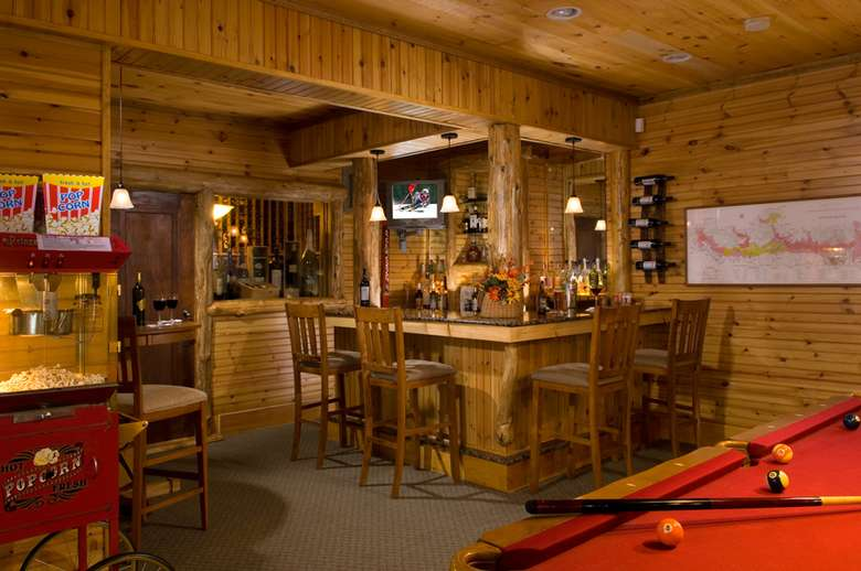 an Adirondck-style kitchen with a bar with chairs and a popcorn machine