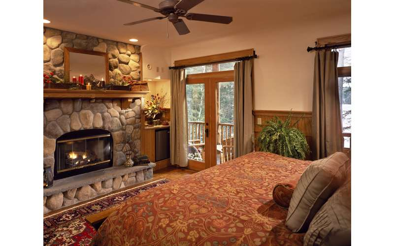 a bedroom with a  stone fireplace and sliding glass doors
