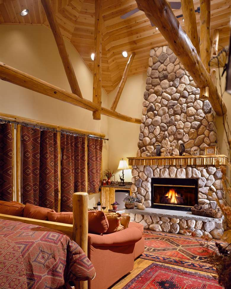 the living room with high ceilings and a fire in the fireplace