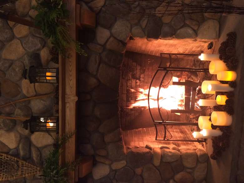 a sideways photo of a fire with white candles in front of it