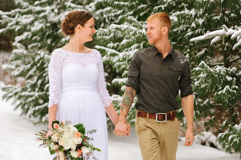 a bride and groom walking hand in hand outside int he snow