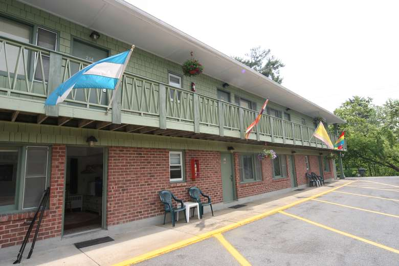 exterior of Community Court Motel with flags outside the front