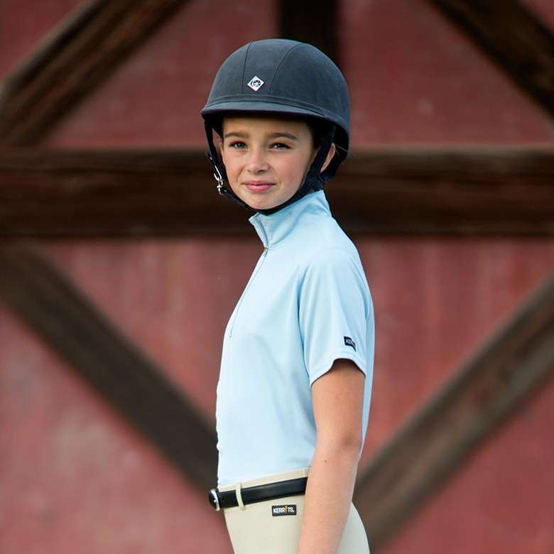 young girl in equestrian apparel standing in front of a barn