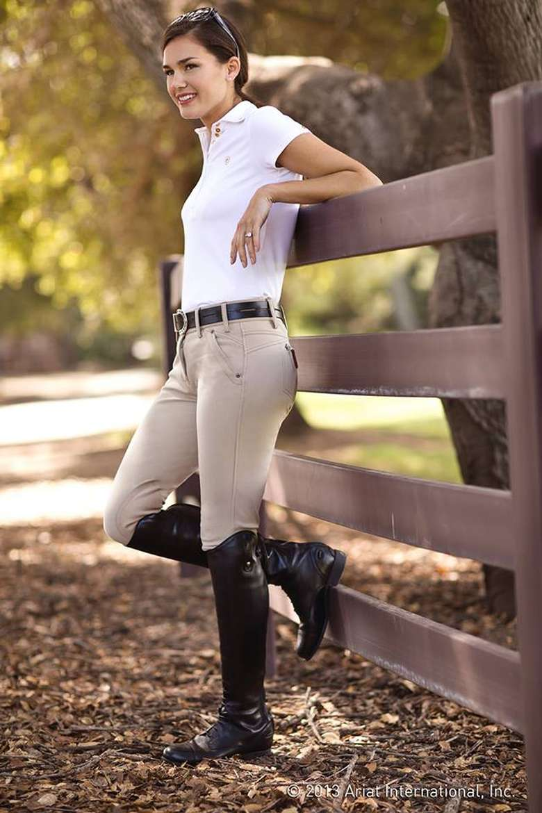 woman in equestrian apparel leaning against a fence
