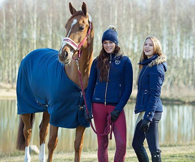 two girls standing with a brown horse wearing a blue blanket
