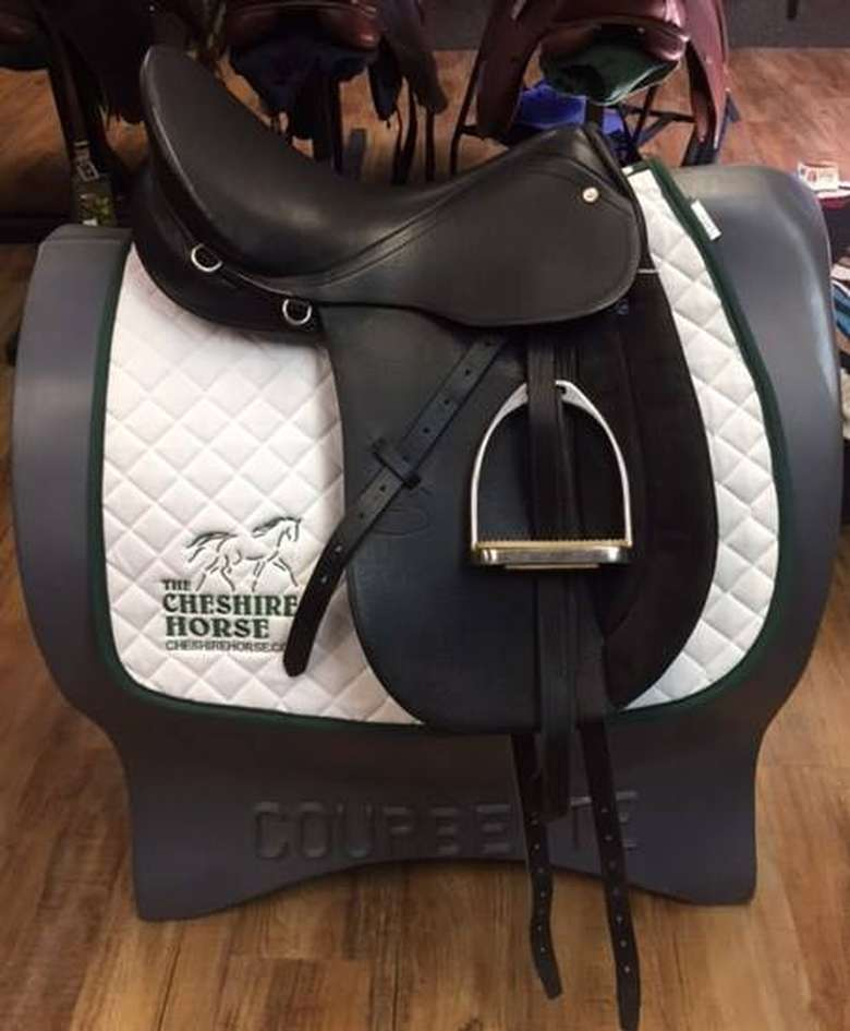 dark brown saddle with a white blanket that has the cheshire horse logo on it
