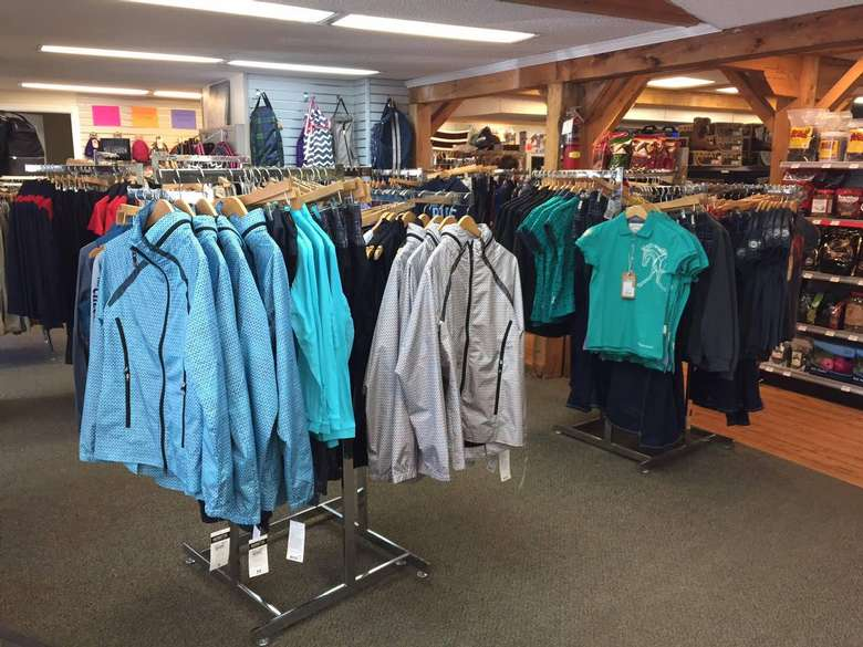 store racks with jackets, t-shirts, and other clothing