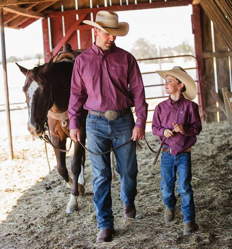 father and son in a barn wearing matching jeans, shirts, cowboy hats, and boots