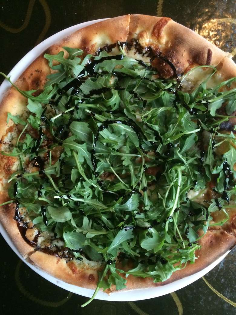 pizza topped with arugula and balsamic