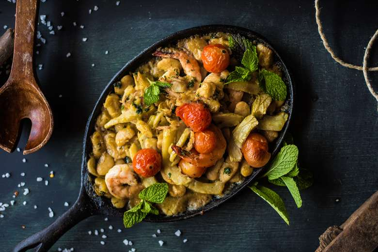 skillet of pasta with cherry tomatoes and shrimp