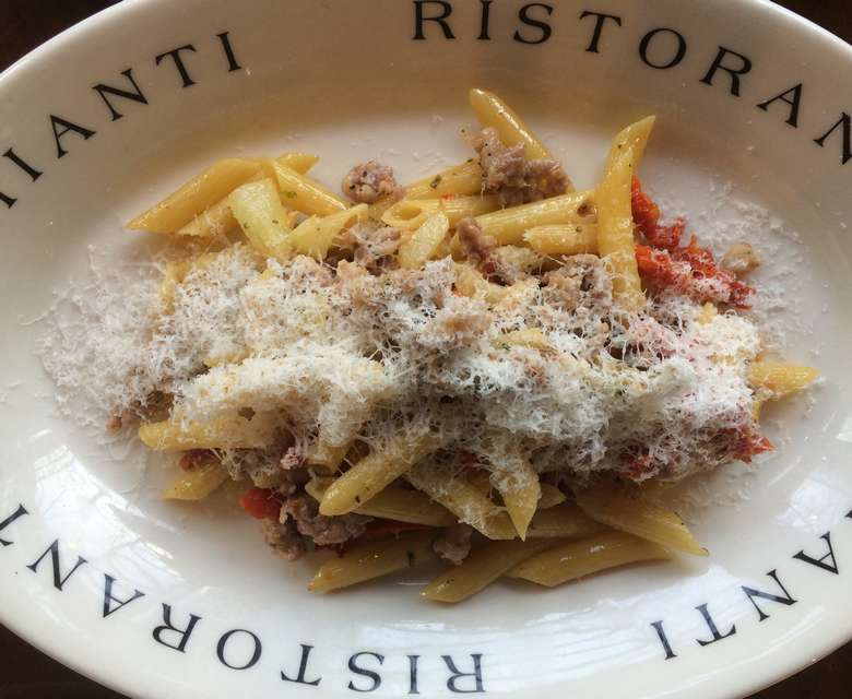 penne pasta with parmesan cheese in a dish that says chianti ristorante on the rim