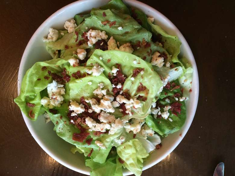 green salad with bacon bits and blue cheese crumbles