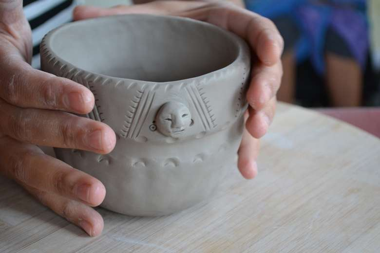 two hands surrounding a clay bowl