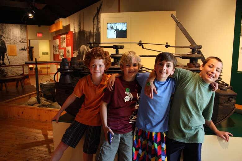 four young boys, arm in arm, standing inside the museum and smiling at the camera