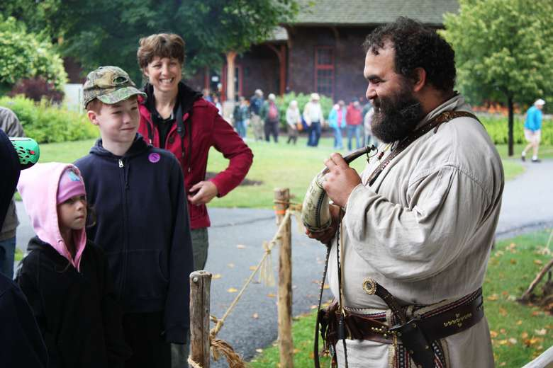 a reenactor dressed as a trapper is talking to two kids with a woman looking on and smiling
