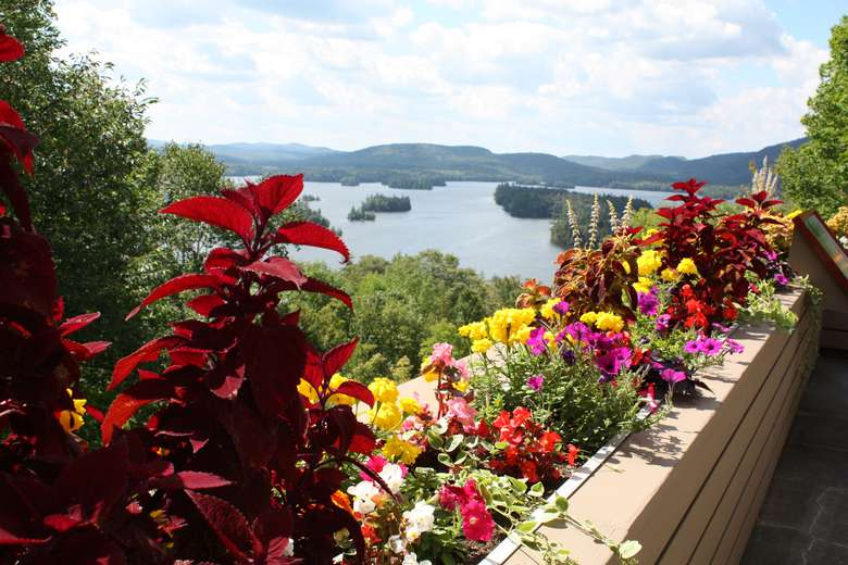 a deck with colorful flowers in flower boxes overlooking a lake surrounded by mountains