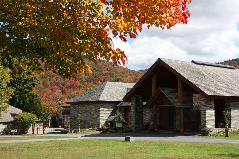 the stone and wood entrance to the Adirondack Experience, there is a tree with fall foliage in front, and mountains with fall foliage behind