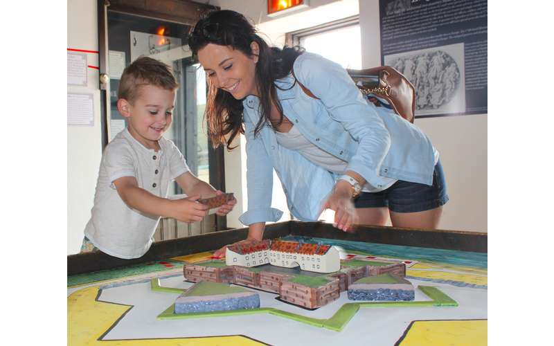 woman showing boy an exhibit of a fort