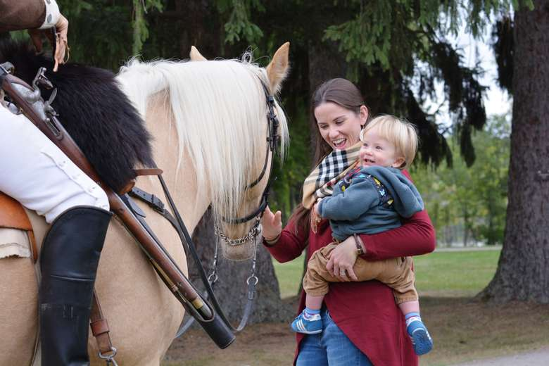 boy and mother smiling petting horse
