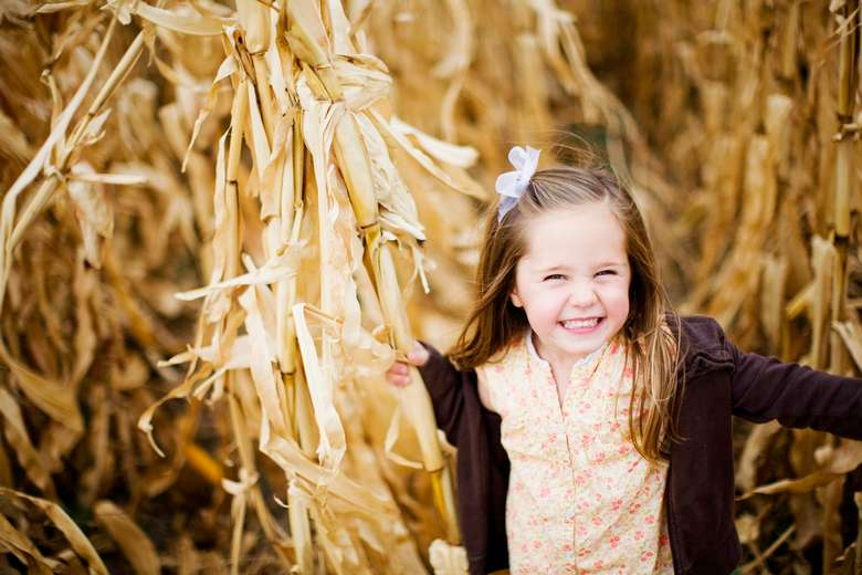 young girl smiling in corn field