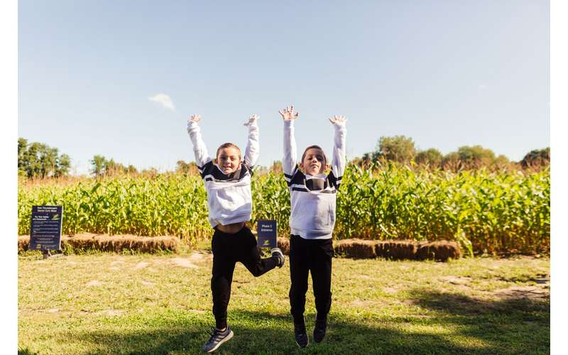 Children jumping in front of corn maze