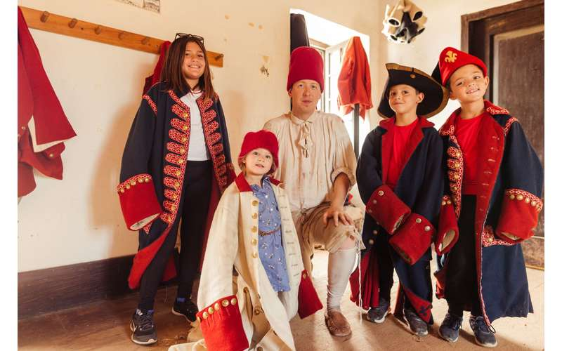 Children with interpreter trying on historic coats