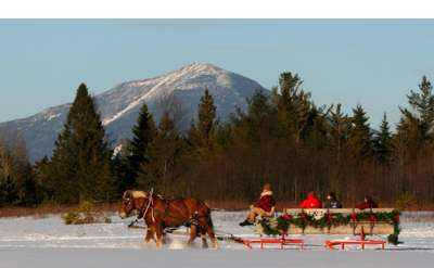 a winter sleigh ride with mountains in the background