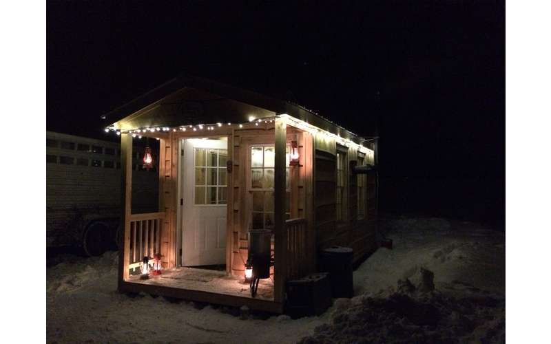 a wooden cabin with lights on it during the evening