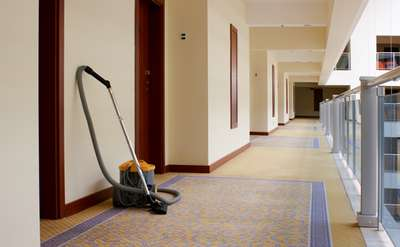 a long carpeted hallway with carpet cleaning equipment against the wall