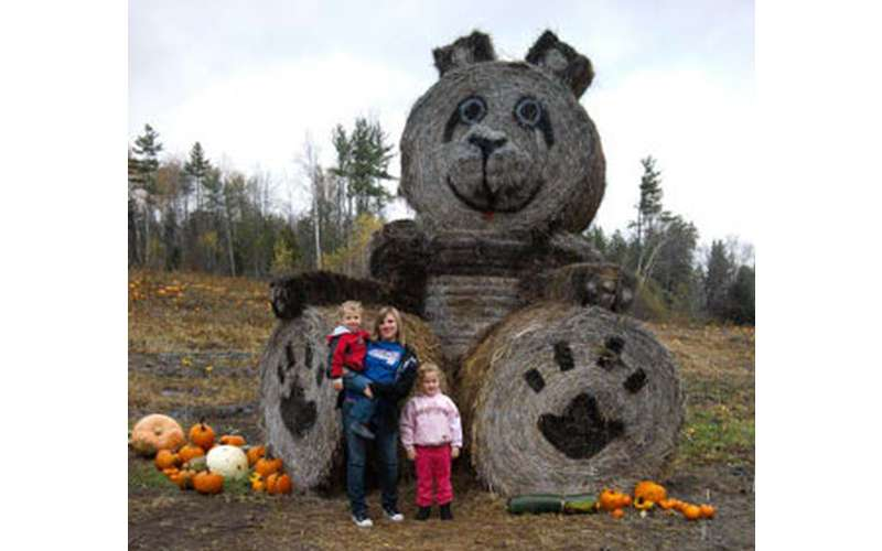 a family posing in front of a giant decorative bear and pumpkins
