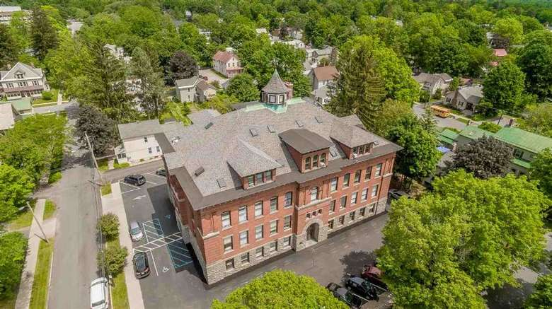 aerial view of a large brick building with trees nearby