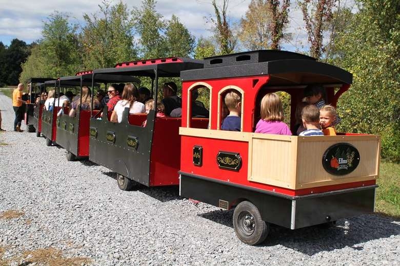 kids and their parents riding on a red and black miniature train