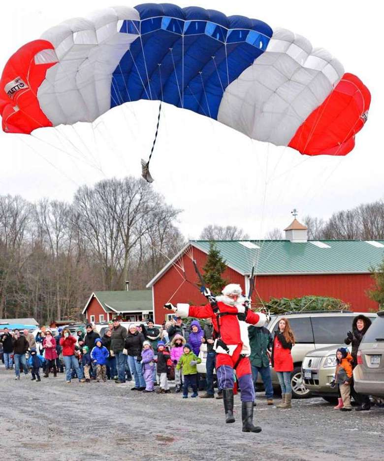 santa parachuting down on a red white and blue parachute