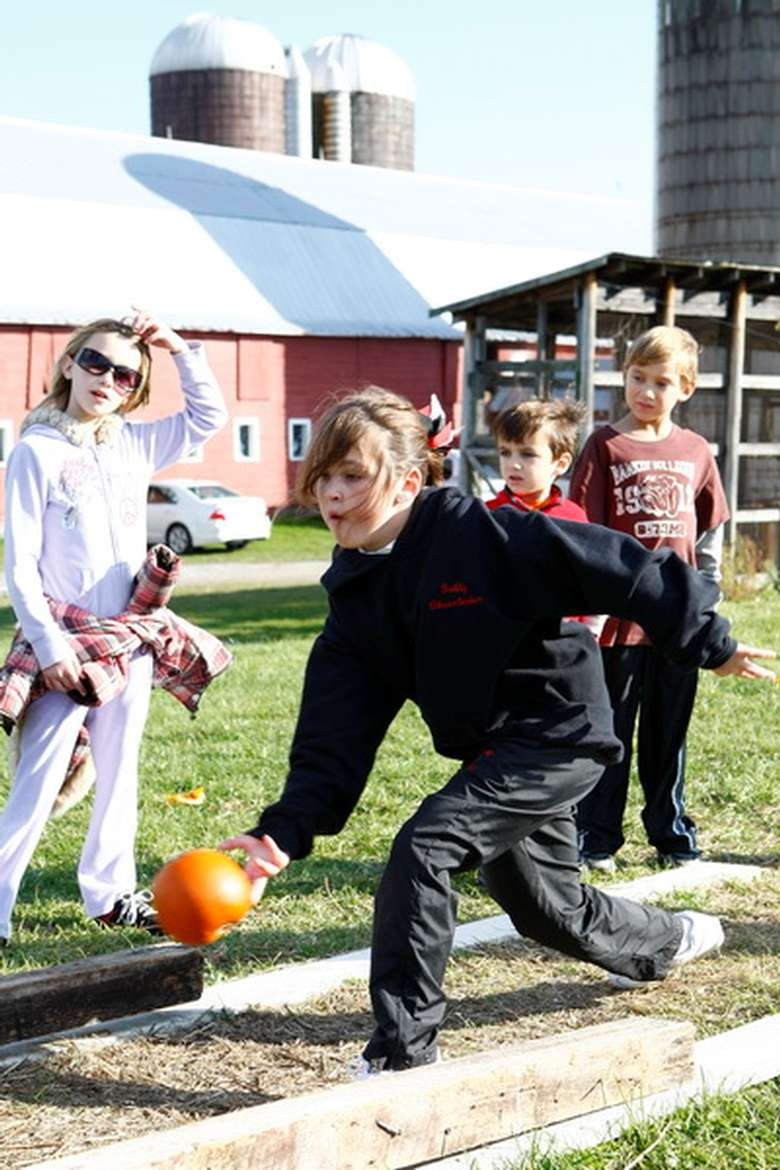 one child bowling with a pumpkin while other kids look on