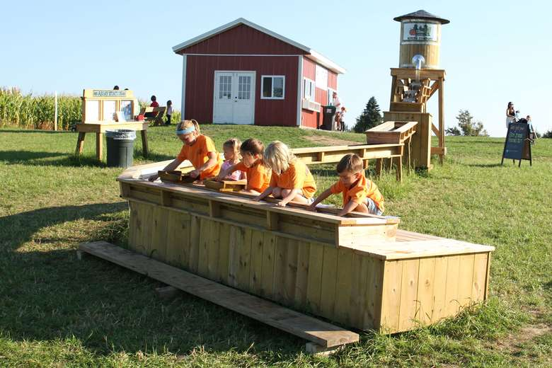 kids in orange shirts mining for gemstones in a trough
