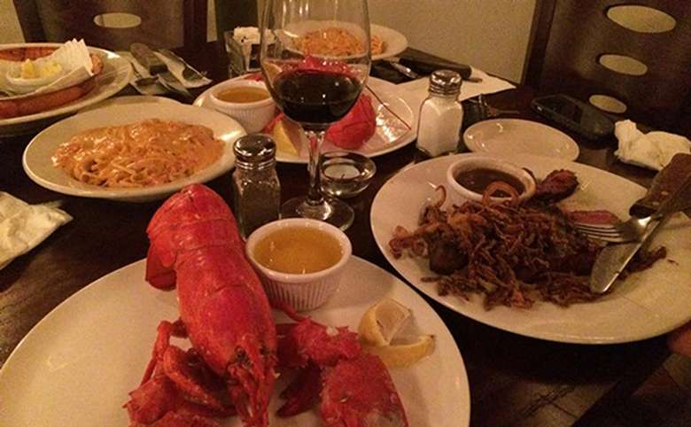plates with steak, lobster, and pasta on a restaurant table