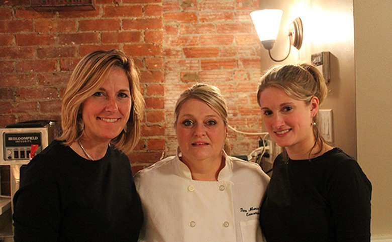 a chef and two servers smiling