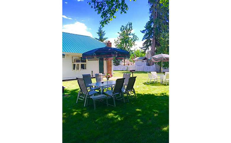 Backyard with two outdoor dining tables and chairs. Each has an umbrella.
