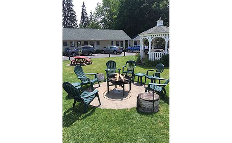 A raised fire pit surrounded by green chairs and small tables. There is a white gazebo, picnic table and lodging units in the background.