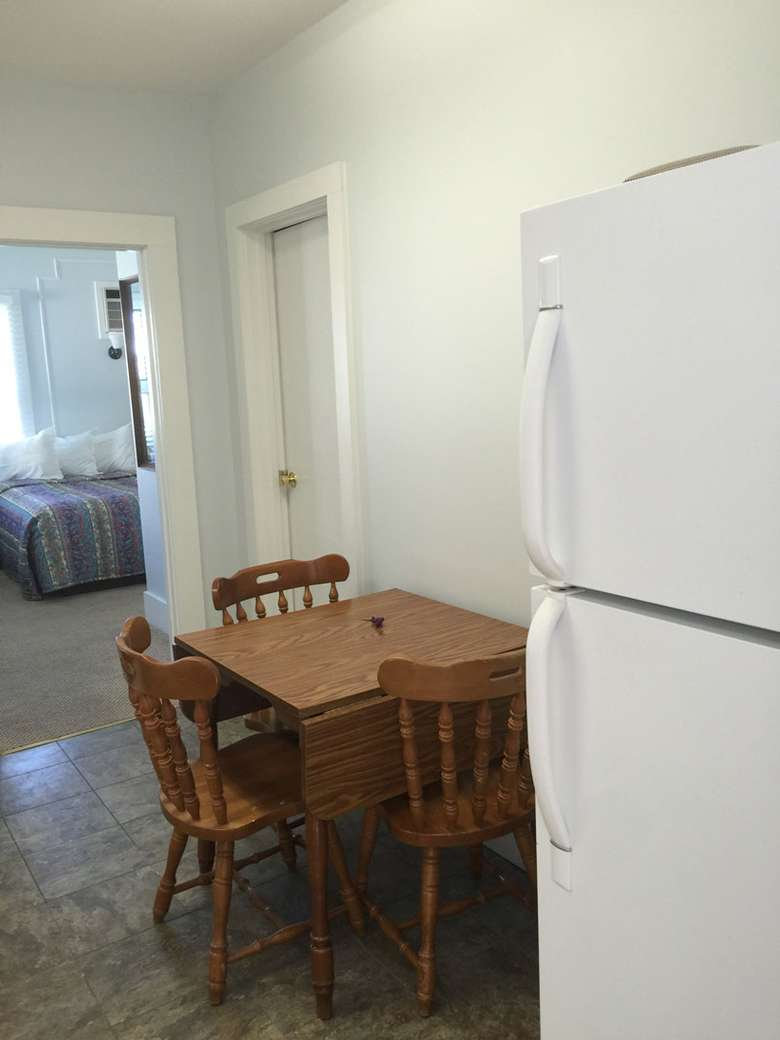 Drop leaf dining table with three chairs next to a large white refrigerator. A bedroom can be seen in the distance