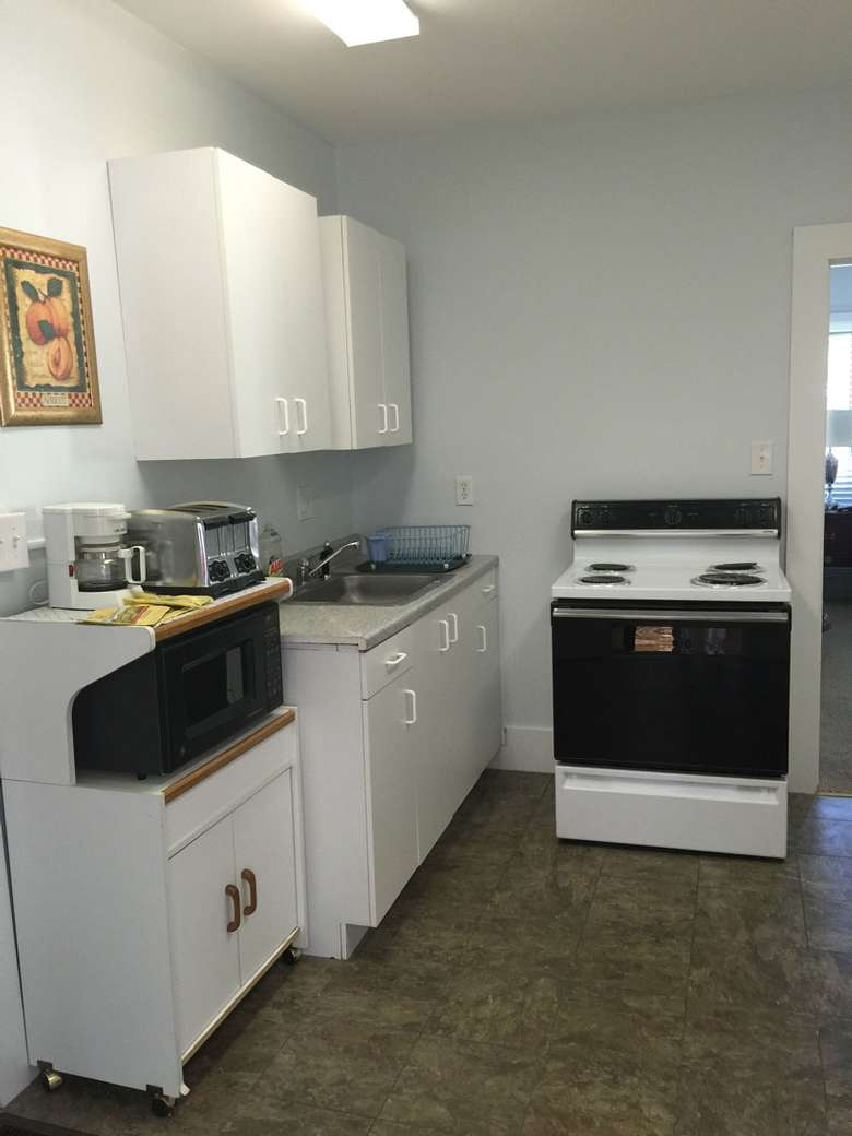 A range with stove top and oven, a microwave and microwave stand, coffee maker, four-slice toaster, sink and several white cupboards