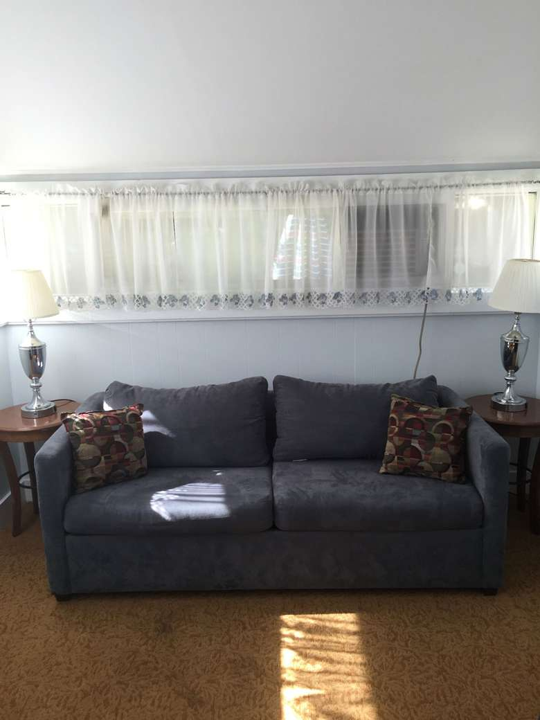 A blue couch in front of windows with end tables and lamps on either side