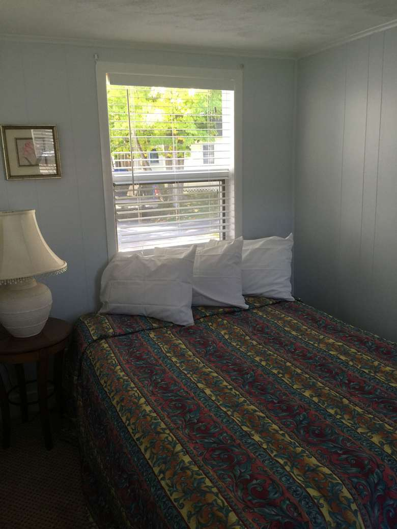 A full-size bed in front of a window in the second bedroom. There is a nightstand with lamp to the left of the bed.