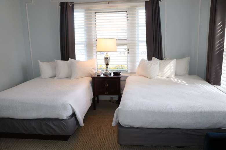 view of both beds in first bedroom, there's a nightstand, lamp and large window in between the beds