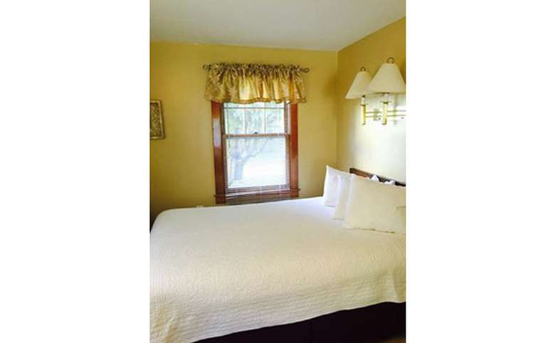 a bedroom with yellow walls, and a full-sized bed with a white bedspread
