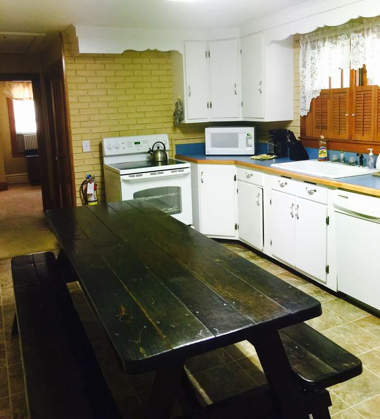 a large kitchen with white cupboards, blue countertops and a dark wooden picnic-style dining table