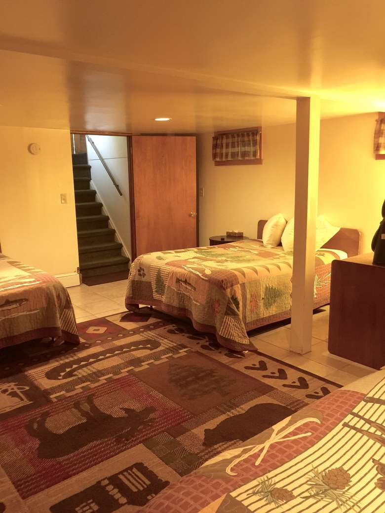 same bedroom as previous image, from another angle, showing stairs leading down to the room