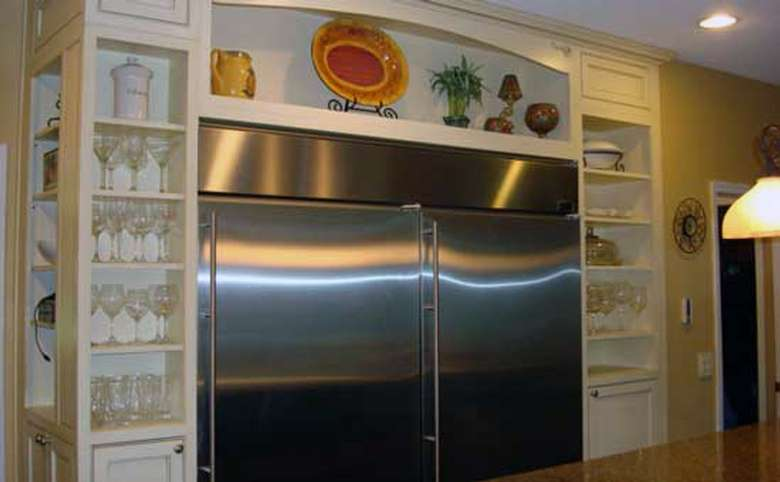 Stainless steel commercial-sized refrigerator surrounded by shelves with glassware