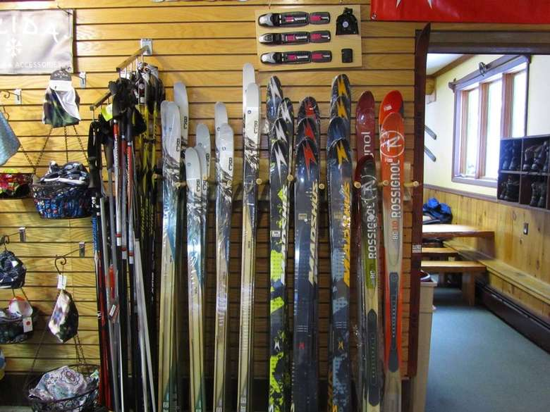 row of skis next to wall with ski equipment
