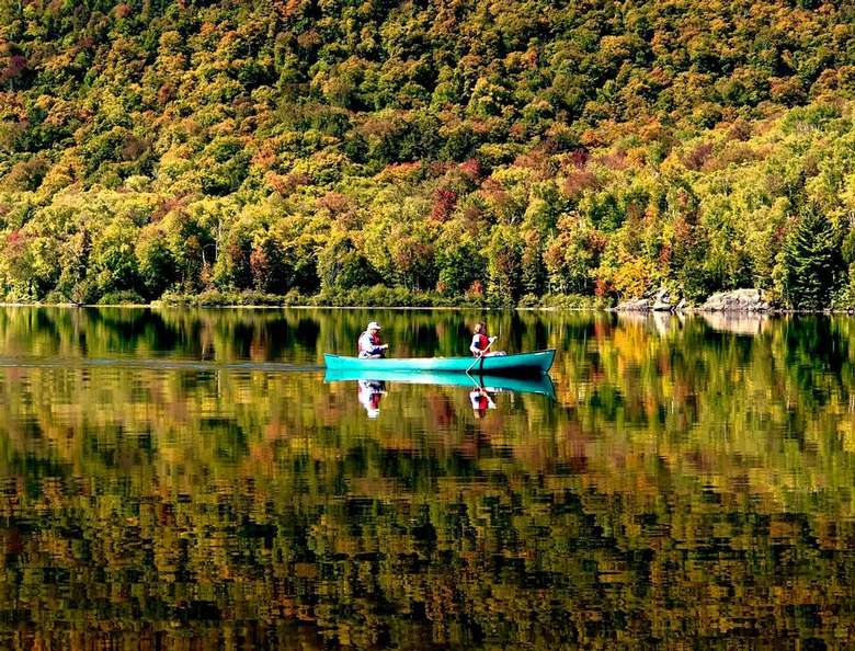 two people in a canoe on a lake with fall colors across trees in the background